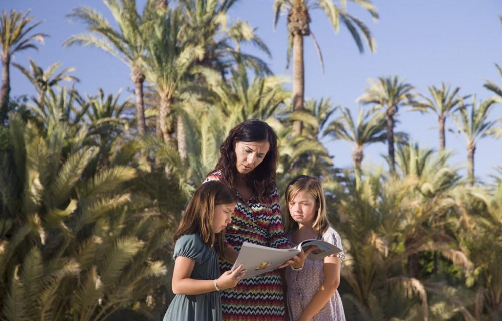 costa blanca palmeral elche familia leyendo en el parque